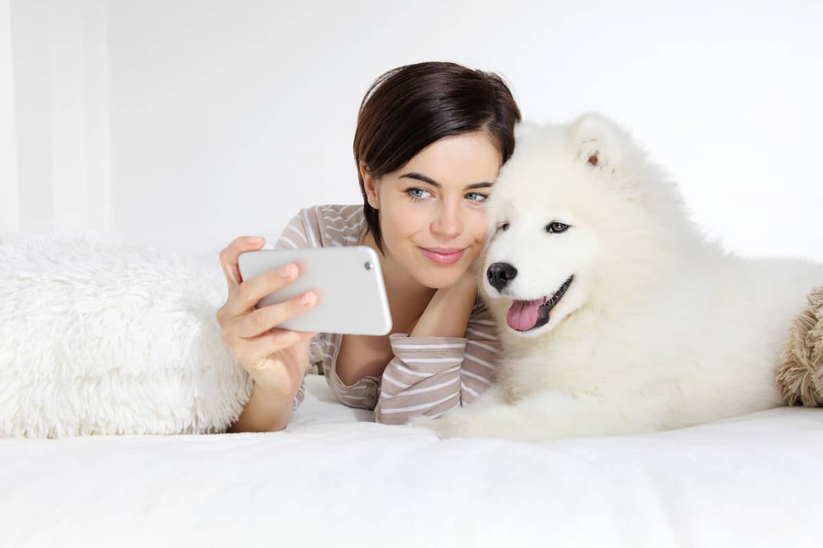 selfie smiling woman with pet dog lying in bed